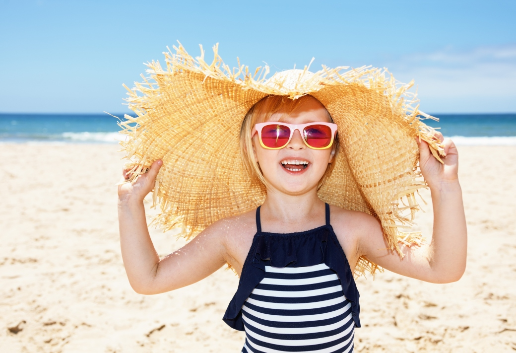 Smiling girl in swimsuit and straw hat on white beach